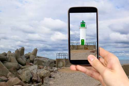Man is taking photo of lighthouse
